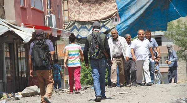 مسلحان من حزب العمال الكردستاني في أحد شوارع بلدة سيلوان قرب مدينة ديار بكر ذات الغالبية الكردية في جنوب شرقي تركيا أمس (رويترز)