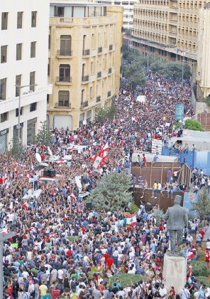 People wave Lebanese flags as they protest against corruption and against the government's failure to resolve a crisis over rubbish disposal, near the government palace in Beirut, Lebanon August 23, 2015. Lebanese security forces fired water cannon at protesters demonstrating against the government near Prime Minister Tammam Salam's offices in Beirut on Sunday, live television pictures showed. REUTERS