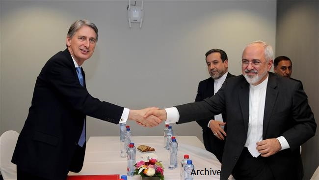 British Foreign Secretary Philip Hammond Mohammad shakes hand with Javad Zarif (R)   on March 16, 2015 in Brussels